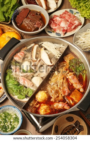 Double flavor hot pot on the table - stock photo