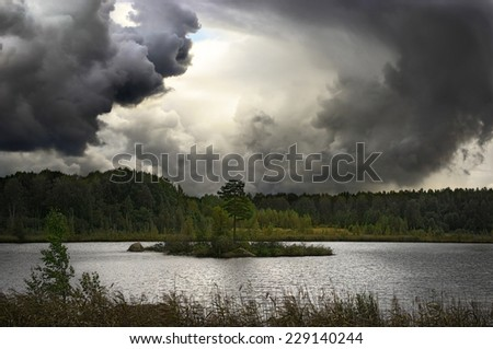 dragon shaped monster cloud swirl over lake island, tornado, thunderstorm                             - stock photo