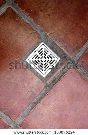 drain. Water flows through a metal drain hole cover buried in the pavement. - stock photo