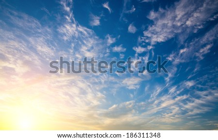 Dramatic sunset sky with sun and clouds. - stock photo