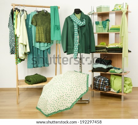 Dressing closet with green clothes arranged on hangers and shelf, autumn outfit on a mannequin. Wardrobe full of all shades of green clothes and accessories. - stock photo