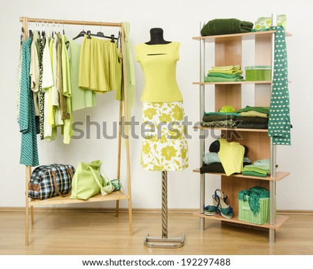 Dressing closet with green clothes arranged on hangers and shelf, neon green outfit on a mannequin. Wardrobe full of all shades of green clothes and accessories. - stock photo