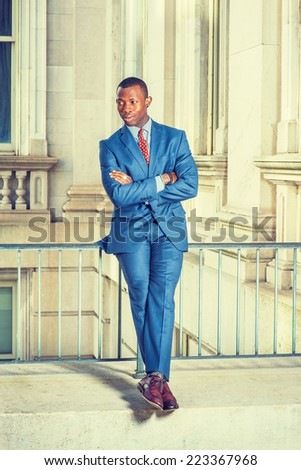 Dressing formally in blue suit, patterned undershirt, tie, leather shoes, short haircut, crossing arms and legs, a young black businessman is sitting on railing in office building, relaxing, - stock photo