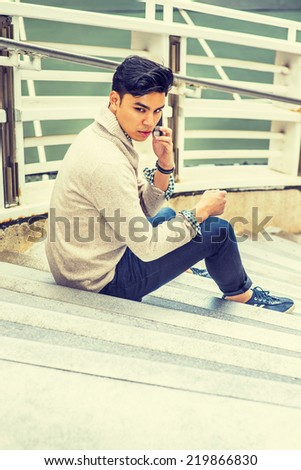 . Dressing in kitted sweater with shawl collar cardigan, jeans, rolling over cuff, a young guy is sitting on stairs by fence, talking on mobile phone, looking back.  - stock photo