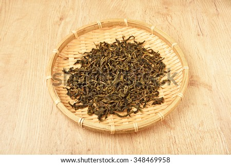 Dried tea leaves in a bamboo basket - stock photo