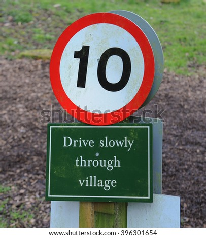 """""""10"""" + """"Drive Slowly Through Village"""" Signs in the Arboretum near The Rural Village of Batsford near Moreton in Marsh within The Cotswolds, Gloucestershire, England, UK - stock photo"""