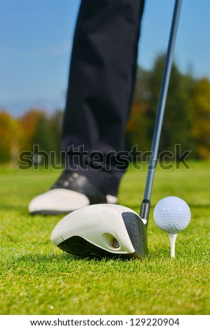 Driver with golf ball on a tee and grass - stock photo