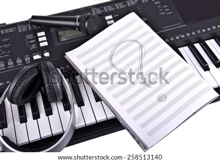 ?eadphones, a microphone and a notebook for musical notes with a question mark is on the synthesizer - stock photo