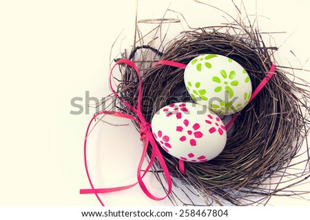 Easter eggs with bright tapes in a nest on white background - stock photo