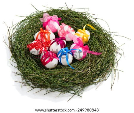 easter eggs with ribbons in nest made of green grass isolated on white