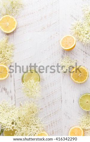Elderflower cordial and ingredients.  Homemade elder flower cordial with lemons and elderflowers  on a rustic table. Top view with copyspace in the middle - stock photo