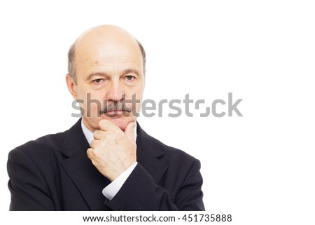 elderly man in a black suit thoughtfully rubs his chin in his hand - stock photo