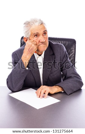 Elderly man lost in deep thought holding a pen and a sheet of paper on white - stock photo