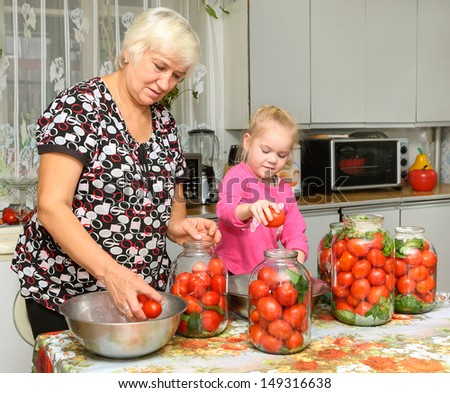 elderly woman and a child  preparing canned tomatoes