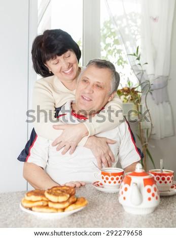 elderly woman and man having breakfast in   kitchen. - stock photo
