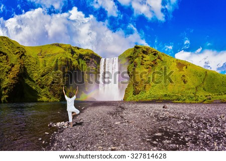 "Elderly woman performs asana ""tree"" of hatha yoga before falling water. Grand waterfall with rainbow in the water mist Skogafoss - stock photo"