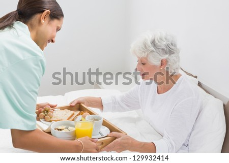 Elderly woman taking a breakfast with home nurse in the bedroom - stock photo