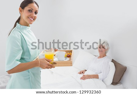 Elderly woman with home nurse in the bedroom - stock photo