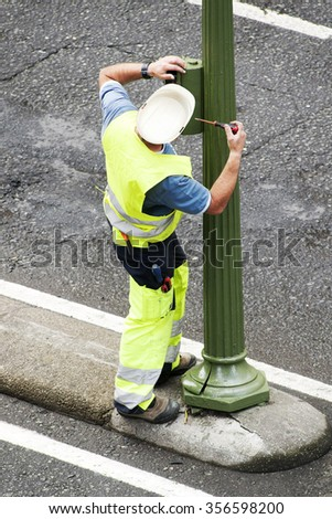electrician worker of utility company to repair traffic lights in the street city - stock photo
