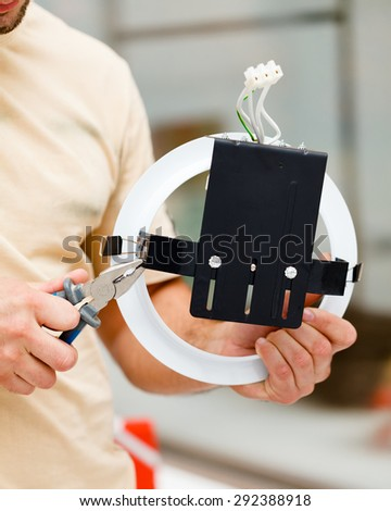 Electrician working with pliers mounting a light. - stock photo