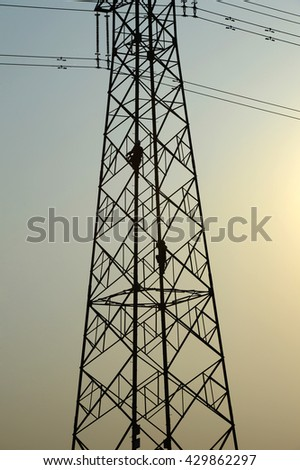 Electricity workers work on high voltage towers