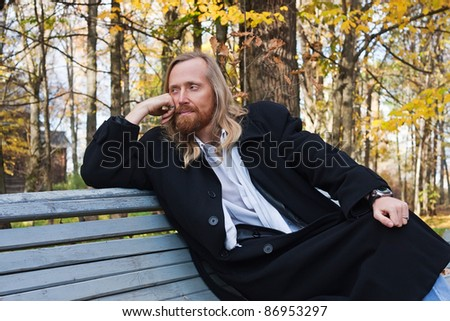 Elegant man sitting on the wooden bench in autumn park