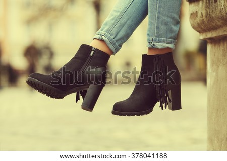 Elegant outfit. Closeup of stylish black suede ankle boots. Fashionable girl on the street. City lifestyle. Female fashion. Toned - stock photo