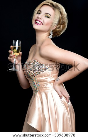 Elegant young woman with a champagne glasses at celebration - stock photo