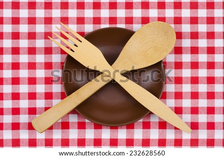 empty brown plate spoon and fork on a checkered tablecloth - stock photo