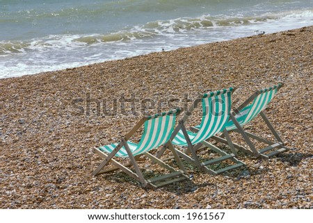 3 empty deck chairs on the beach