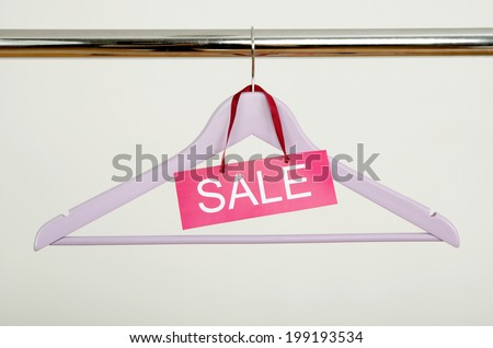 Empty hanger on a rack of clothes with the sale sign. Close up on purple wood hanger, clearance concept.  - stock photo
