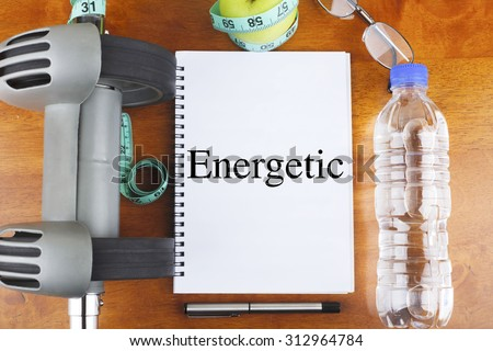 """""""Energetic"""" text on notebook with delicious green apple, measure tape, spectacle, a bottle of mineral water, and bodybuilding tools on wooden background - healthy, exercise and diet concept - stock photo"""