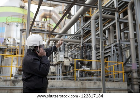 engineer pointing against pipeline inside large oil refinery - stock photo