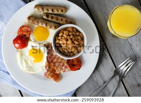 """English breakfast or a """"full English breakfast"""". Breakfast with fried eggs, bacon, sausages, beans, grilled tomatoe and orange juice. - stock photo"""