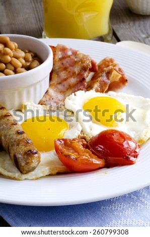 """English breakfast or a """"full English breakfast"""". Breakfast with fried eggs, bacon, sausages, beans, grilled tomatoes and orange juice. - stock photo"""
