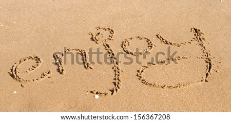 """Enjoy"" written in the sand"
