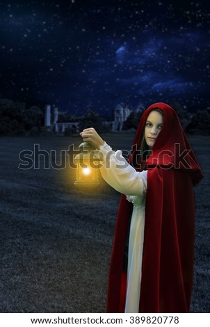 1800 era woman at night with lantern - stock photo