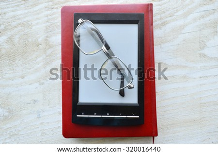 ereader with  glasses on wooden table - stock photo