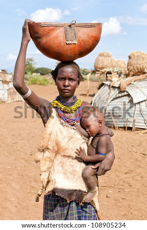 ETHIOPIA - AUG 15:  Women of ethnic Erbore with her child,the ethnic groups in the The Omo valley Could disappear Because of Gibe III hydroelectric dam. on Aug 15, 2011 in Omo Valley, Ethiopia. - stock photo