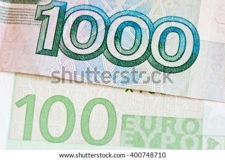 100 euro and 1000 roubles banknotes, close up - stock photo
