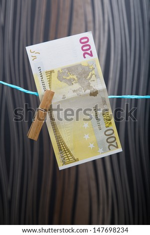 """200 Euro banknote fixed on a clothes line with a wooden peg - """"Safari"""" background - stock photo"""