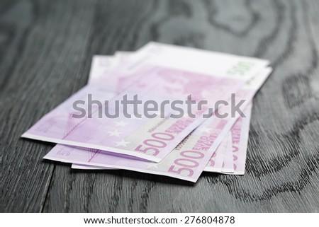 500 euro bills on wood table - stock photo