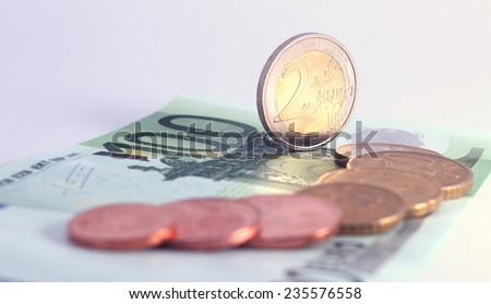 2 euro coin standing vertically on 100 euro note near row of complete set of euro coins. symbol for european economy, business, banking and finance - stock photo