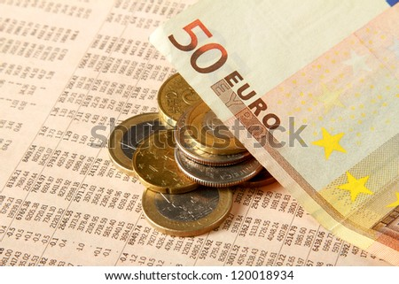 Euro coins and financial newspaper - stock photo