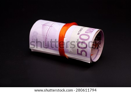 500 euro money in  red ribbon on black - stock photo