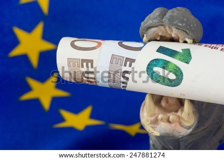 10 Euro note in mouth of a hippo figurine - stock photo