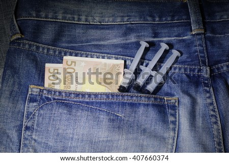100 Euro with medical syringe in the pocket of jeans - stock photo