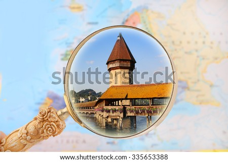 Europe with magnifying glass looking in on Switzerland, Chapel Bridge in Lucerne - stock photo