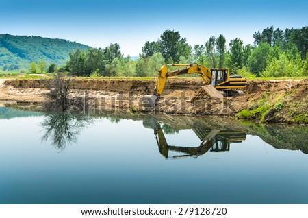 Excavator in gravel pit  - stock photo