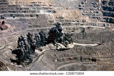 excavators,trucks and heavy machinery in open cast mine after blast among dust and smoke - stock photo